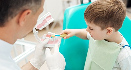 A little boy brushing the teeth of a mouth mold with a children's dentist in Bellevue