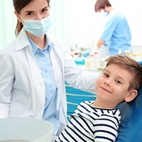 A little boy smiling in the dentist's chair as the dental professional prepares to place dental sealants