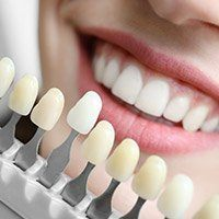 Closeup of patient's smile compared with tooth color chart