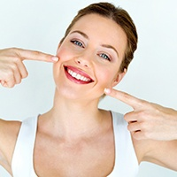 Woman pointing to her beautiful teeth.