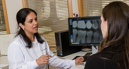 Dr. Taneja and patient looking at dental x-rays