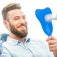 Man smiling in mirror at dental office